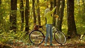 De herfstvrouw in de herfstpark met groene trui Openlucht atmosferische manierfoto van jonge mooie dame in de herfst stock footage