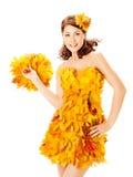 De herfstvrouw in kleding van esdoornbladeren over wit Royalty-vrije Stock Afbeeldingen