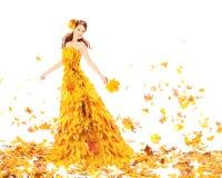 De herfstvrouw in manier gele kleding van esdoornbladeren Stock Foto