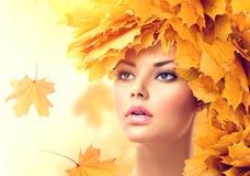 De herfstvrouw met geel bladerenkapsel Royalty-vrije Stock Afbeeldingen