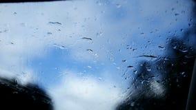 De herfstweg op een regenachtige dag - defocused achtergrond Het bewegen waterdrops zich in de wissers van het windscherm stock video
