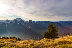 De herfstzonsondergang over een grasrijke bergkant stock foto's