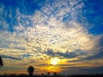 De herfstzonsopgang met mist De stralen van de zon van de ochtendzon breken door de wolken tegen de blauwe hemel stock afbeeldingen