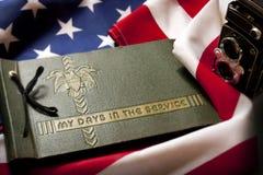 De Herinnering van de herdenkingsdagveteraan met Legerdienstalbum en vlag. Stock Foto