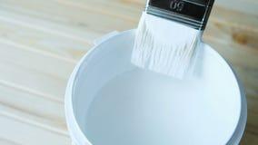 De hersteller dompelt een schone borstel in witte verf onder stock footage