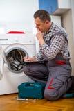 De hersteller herstelt een wasmachine op de witte achtergrond stock foto