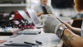 De hersteller verzamelt smartphone na reparatie door alle details in workshop op te nemen stock footage