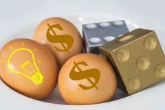 De het Amerikaanse dollarteken en lamp op eieren met dobbelen Stock Afbeeldingen