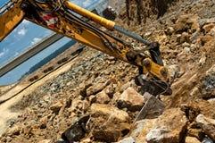 De het bewegende zand en rotsen van de graafwerktuigingenieur met op zwaar werk berekende lepel Stock Foto