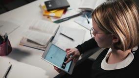 De het close-upa schoolmeisje of student gebruiken een tablet, schalen en navigeren door de verbindingen Zij ` s die haar thuiswe stock footage
