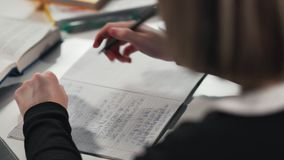 De het close-upa schoolmeisje of student schrijven in een werkboek Zij ` s die haar thuiswerk doen stock video