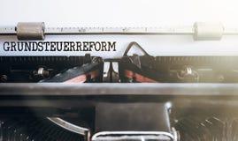 De het Duitse die bezit van woordgrundsteuerreform of hervorming van de landbelasting op oude schrijfmachine wordt geschreven stock afbeeldingen