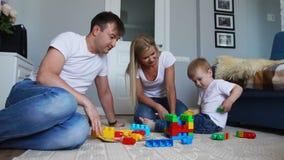 De het gelukkige mamma en baby van de familiepapa 2 jaar die lego in hun heldere woonkamer spelen Slow-motion schietende gelukkig stock footage