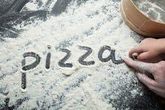 De het handmamma en baby schrijven het woord 'pizza 'op de bloem, zwarte achtergrond royalty-vrije stock afbeeldingen