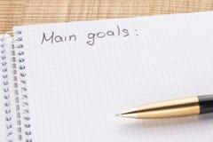 De het hoogste notitieboekje en pen van de meningswerkplaats op houten lijstachtergrond, retro effect De inschrijving - hoofdoals stock afbeeldingen