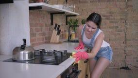 De het huisverbetering, glimlachende vrouwenhuishoudster in rubberhandschoenen voor het schoonmaken veegt stoffig meubilair op ke stock videobeelden