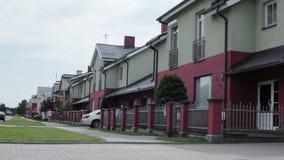 De het hulpmiddeldoos van de jonge mensenholding loopt langs twee verdiepings concrete huizen in daglicht stock footage