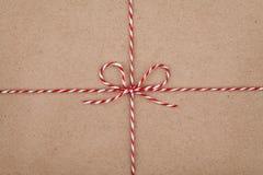 De het Kerstmiskoord of streng bond een boog op kraftpapier-document textuur vast stock afbeelding