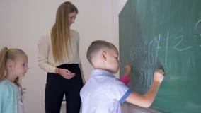 De het kindleerlingen van de opvoederhulp met krijt in hun handen schrijven letters en getallen op bord bij de les in school stock video