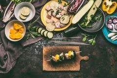 De het kippenvlees en groenten doorsteken op scherpe raad op de donkere achtergrond van de keukenlijst met platen en kommeningred Stock Afbeeldingen
