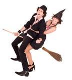 De het meisjesheks van Halloween op bezem draagt de mens. Stock Foto's