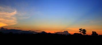 De het mooie kleurrijke landschap van de panoramazonsondergang en berg van de silhouetboom in de tijd van de hemelschemering Royalty-vrije Stock Afbeelding