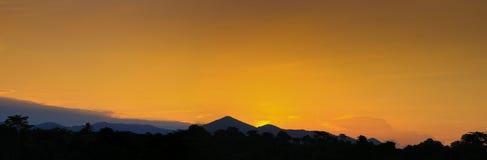 De het mooie kleurrijke landschap van de panoramazonsondergang en berg van de silhouetboom in de tijd van de hemelschemering Royalty-vrije Stock Foto