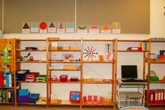 De het onderwijsmaterialen liggen op planken in een klaslokaal stock foto's
