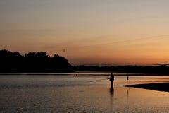De het plaatsen de avondzon en visser Royalty-vrije Stock Afbeeldingen