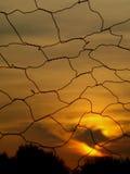 De het plaatsen zon achter het draadnetwerk Stock Afbeelding