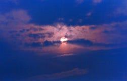 De het plaatsen zon op de donkerblauwe hemel die in de wolken verbergen Royalty-vrije Stock Fotografie