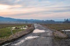 De het plaatsen zon over een landweg Stock Afbeelding