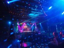 De het spelgitaar van musicusTavana en zingt op stadium Stock Fotografie