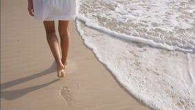 De het verlofvoetafdrukken van vrouwenbenen op het zand, golf reinigt de voetafdrukken stock videobeelden