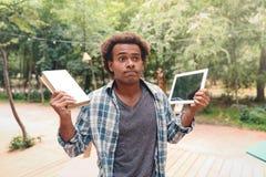 De het verwarde boek en tablet van de mensenholding in openlucht Royalty-vrije Stock Foto