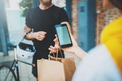 De het voedseldienst van de koerierslevering thuis Vrouw die de geleverde orde controleren geen naamzak met voedsel met mobiele t stock afbeelding