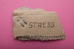 De het woord 'spanningen geschreven op een oud gescheurd karton is geïsoleerd op een roze achtergrond stock foto's