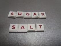 De het woordsuiker en zout maakten van kruiswoordraadseltegels Stock Foto