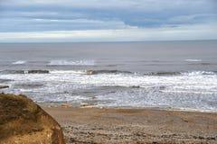 de het zandkust van de strandrots bij ziet oceaan stock fotografie
