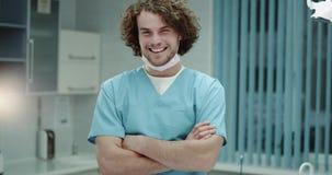 In de het ziekenhuis jonge arts of de chirurgen zeer charismatisch met het grote glimlachen, het gelukkige kijken door de camera stock video