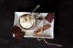 De hete chocolade in een mok met handvat, de kruiden en de chocoladestukken op een wit plateren hierboven op een zwarte achtergro Royalty-vrije Stock Afbeelding
