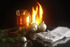 De hete drank in een glas, de Kerstmisballen, de spartakken en de warme eigengemaakte vuisthandschoenen op een open haard steken  stock fotografie