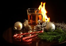 De hete drank in glas, de Kerstmisballen, de spartakken en de snoepjes op een open haard steken achtergrond in brand Nieuwjaar en royalty-vrije stock foto