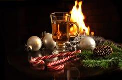 De hete drank in glas, de Kerstmisballen, de spartakken en de snoepjes op een open haard steken achtergrond in brand Nieuwjaar en royalty-vrije stock fotografie