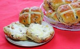De Hete Dwarsbroodjes van Pasen één uitgespreid met boter Stock Foto's