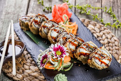 De hete gebraden die Sushi rolt en maki met gerookte paling, roomkaas, avocado en wasabi op zwarte steen op bamboemat wordt gepla Stock Fotografie
