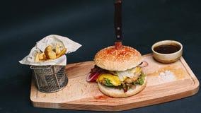 De hete hamburger met frieten en de rode die saus zijn op de raad, met een mes wordt doordrongen, en klaar om in 4k resolutie bin stock videobeelden
