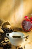 De hete het koffiekop en ontbijt bakten croissants en rood klokteken op de klok van 6 o ` Stock Afbeeldingen