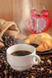 De hete het koffiekop en ontbijt bakten croissants en rood klokteken op de klok van 6 o ` Stock Foto