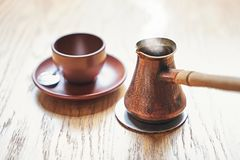 De hete koffie met stoom in oosterse Turkse stijl diende in cezve, een kleine long-handled pot met een gietende lip en kop royalty-vrije stock foto